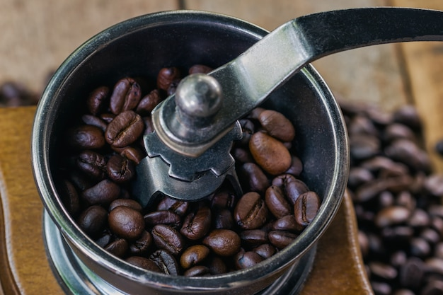 Close up coffee beans on grinding by antique rotary coffee grinder for making homemade