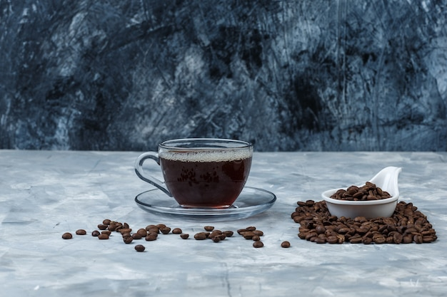 濃紺と水色の大理石の背景にコーヒーのカップと白い磁器の水差しのクローズアップコーヒー豆。水平