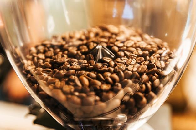 電気コーヒーグラインダー研削盤内のクローズアップコーヒー豆。コーヒーミルは家庭用と事務用の両方です。