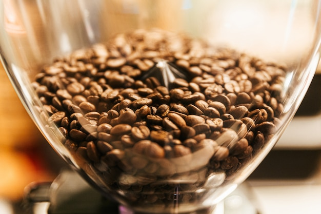 Close-up coffee beans inside electric coffee grinder grinding machine. coffee mill both household and business machine.