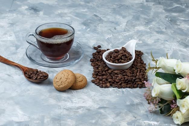 Close-up chicchi di caffè in brocca di porcellana bianca con biscotti, tazza di caffè, fiori