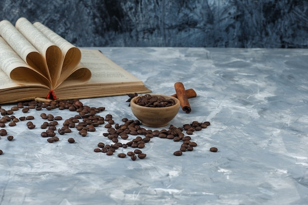 Chicchi di caffè del primo piano nella ciotola di legno con il libro, cannella su fondo di marmo blu scuro e chiaro. orizzontale