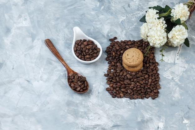 Close-up chicchi di caffè in cucchiaio di legno, brocca in porcellana bianca con biscotti, fiori su fondo in marmo azzurro. orizzontale