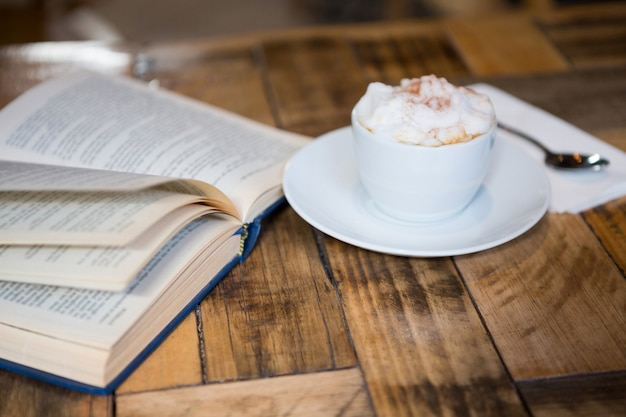 Close-up of coffee cup by open book on table in cafeteria