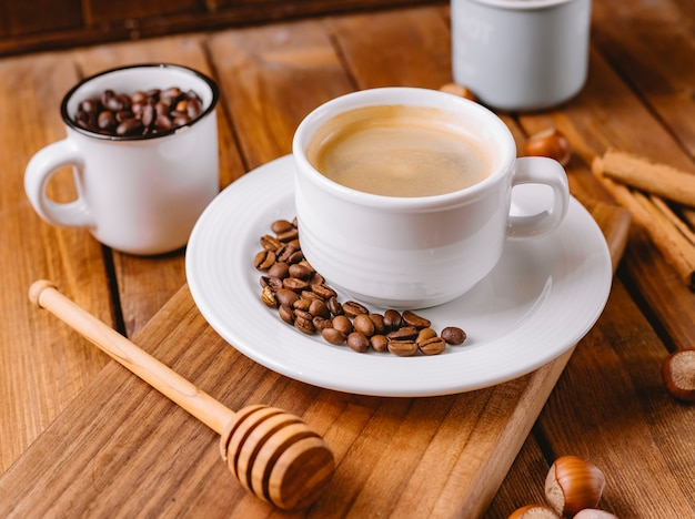 Close up of coffee cup decorated with coffee beans placed on wooden serving board