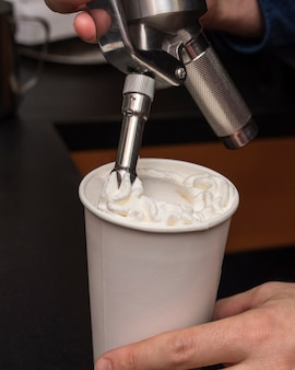 Close-up coffee cup filled with cream