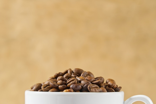 Close up coffee cup full of coffee beans on beige background