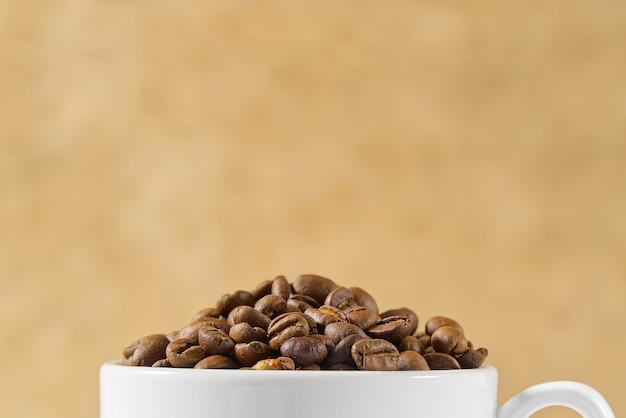 ベージュ色の背景上のコーヒー豆の完全なコーヒーカップを閉じる