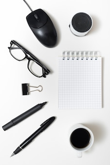 Close-up of coffee cup; office stationery; eyeglass; and bluetooth speaker with notepad over white backdrop
