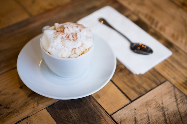 Close-up of coffee cup served on wooden table in cafeteria
