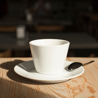 Close-up of coffee cup and spoon on desk