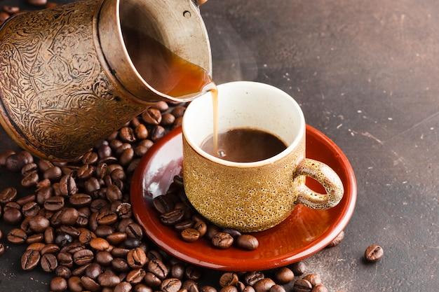 Крупный план кофейной чашки в окружении бобов