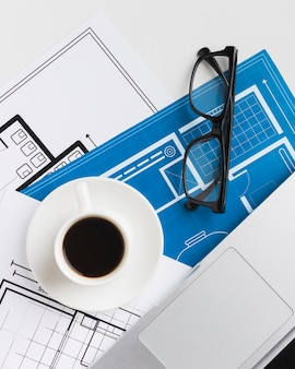 Close-up of coffee cup with blueprints on desk