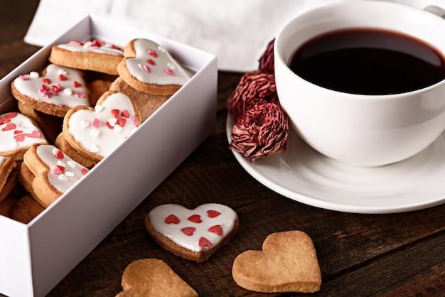 バレンタインデーの茶色の木製の背景に艶をかけられたハート型のクッキーの箱でコーヒーカップを閉じます