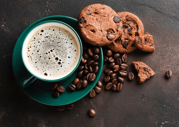 Close-up coffee cup with tasty cookies