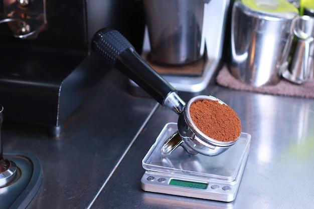 Крупный план, подставка для кофе стоит на кухонных весах, молотый кофе в зернах в фильтре