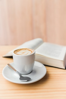 Close-up of coffee latte and open book on wooden table