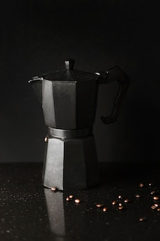Close-up of coffee maker with roasted coffee beans on black background