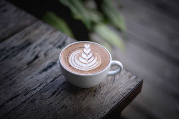 木製のテーブルの上のコーヒーを閉じる
