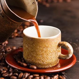 Крупным планом кофе, наливая в чашку