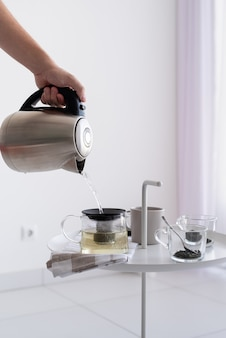 Close up of coffee table and man hand holding kettle, pouring hot water for making tea