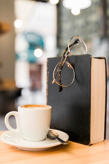 Close-up of coffee with spectacles and book on wooden desk