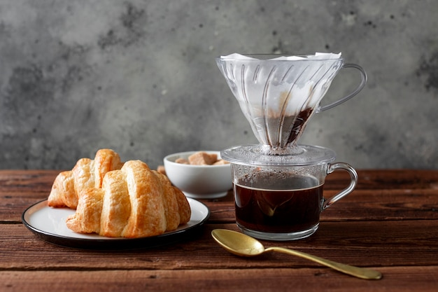 Close-up coffee with tasty croissant