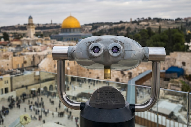 Close-up of coin-operated binoculars with western wall and dome of the rock in the background, old c