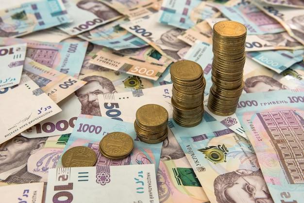 背景としてウクライナのお金の上に横たわる財務チャートとして成長している積み重ねられたコインをクローズアップ。ビジネスの成長と財務コンセプトのために
