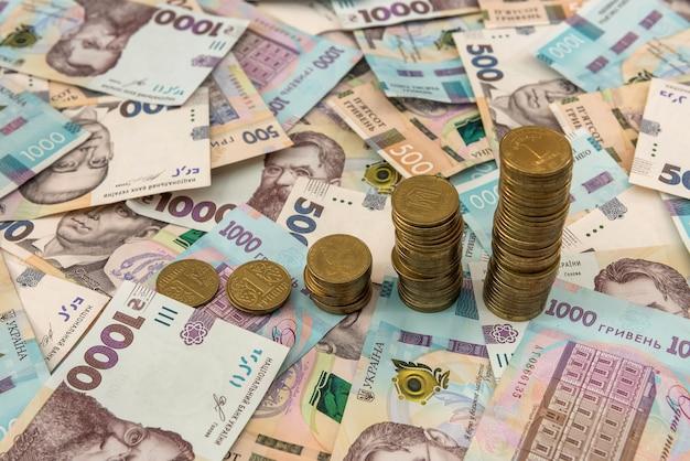 ウクライナのお金の上に横たわる財務チャートとして成長している積み重ねられたコインをクローズアップ