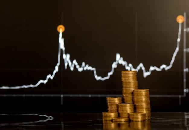 Крупным планом монета сложена, растущая на финансовом графике на фоне экрана ноутбука для роста бизнеса ...