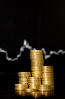 Крупным планом монета сложена, растет на финансовом графике в стене экрана ноутбука