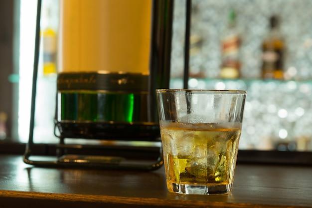 ワインバーの茶色の木製テーブルに黄金のワインの冷たいガラスを閉じます。