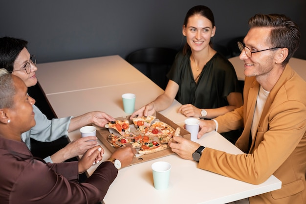 Close up colleagues eating pizza