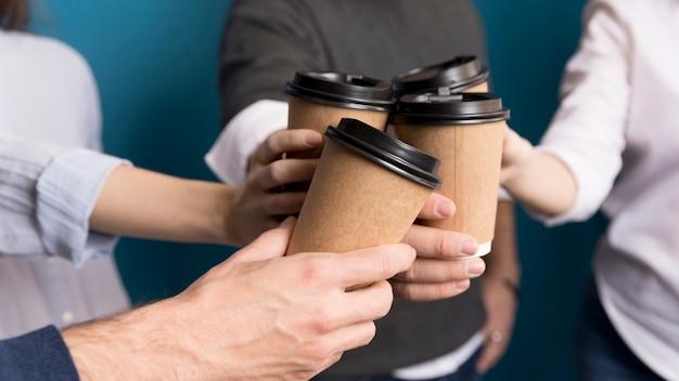 一緒にコーヒーを持っているクローズアップの同僚