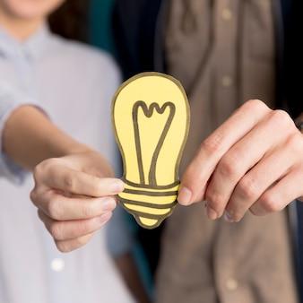 アイデアの光を保持しているクローズアップの同僚