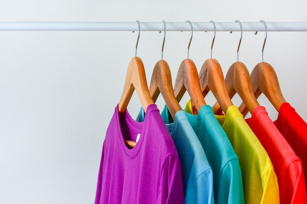 Close up collection of colorful rainbow t-shirts hanging on wooden clothes hanger in closet