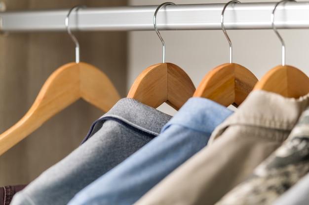 Закройте коллекцию вешалок с одеждой на стойке в шкафу