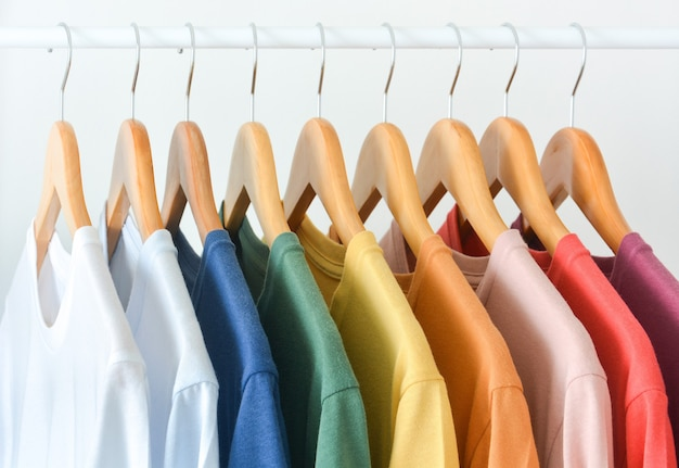 Close up collection of pastel color t-shirts hanging on wooden clothes hanger in closet or clothing rack over white background
