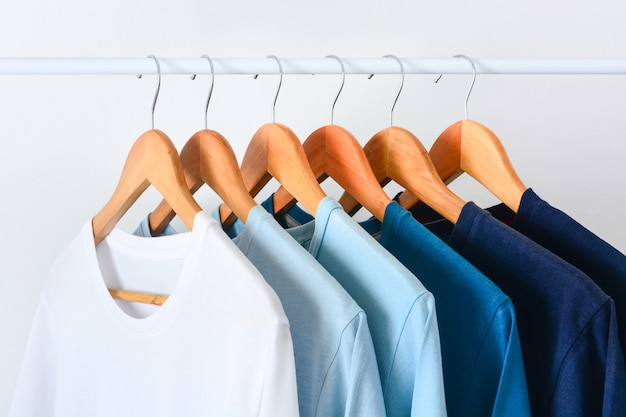 Close up collection shade of blue tone color t-shirts hanging on wooden clothes hanger in closet or clothing rack