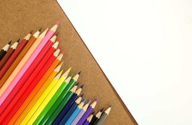 Закройте цветные карандаши с белой пустой бумагой фона обои