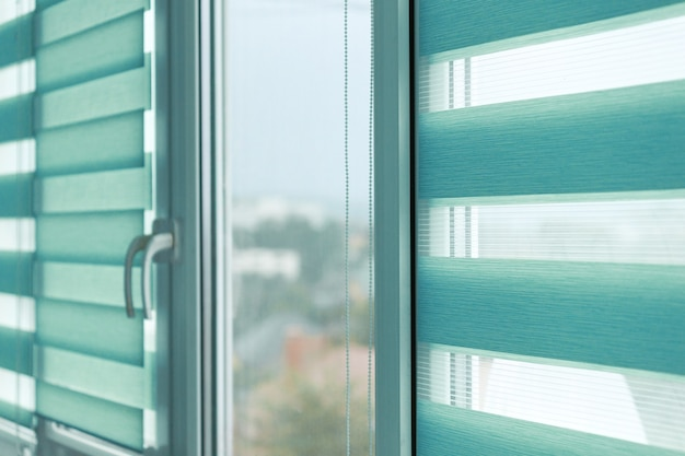 Close up of colored fabric roller blinds on window. roll curtains.