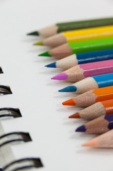 Close-up of colored pencils and notebook