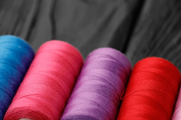 Close up of colored thread coils thread spools background
