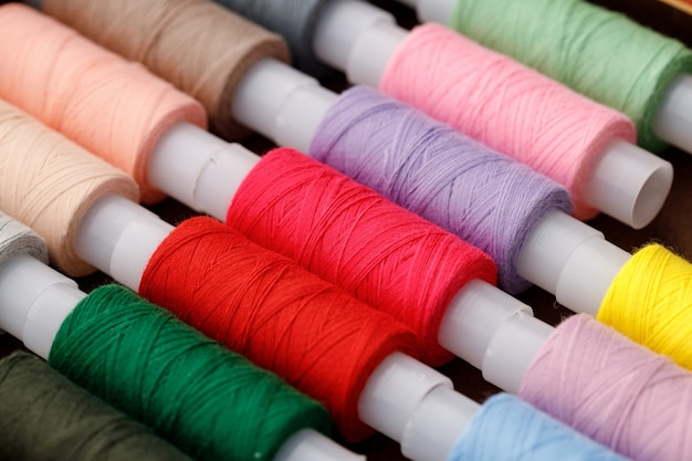 Close up of colored thread coils thread spools surface