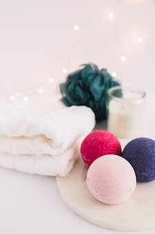 Close-up of colorful bath bombs on white board near napkins and loofah
