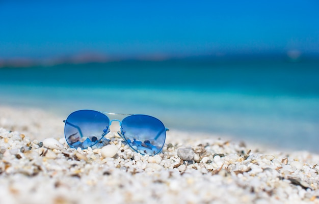 Close up of colorful blue sunglasses on tropical beach.