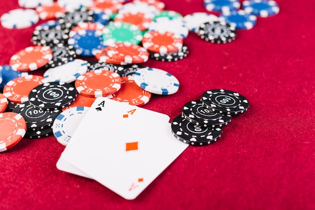 Close-up of colorful chips and two aces playing cards on poker table