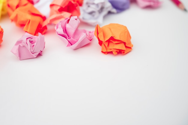 Close-up of colorful crumpled paper on white desk