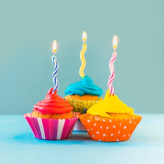 Close-up of colorful cupcakes with illuminated candles on blue backdrop